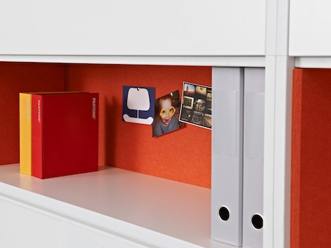 The shelf of a Stem storage unit containing two binders and photos tacked to the orange back panel.