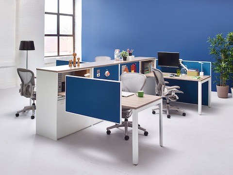 Stem storage units anchor a work area that includes attached peninsula surfaces, blue screens, and grey Aeron office chairs.