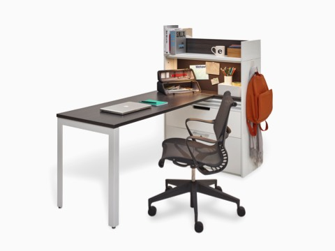 A black Setu office chair complements a workspace consisting of a peninsula surface attached to a Stem storage unit.