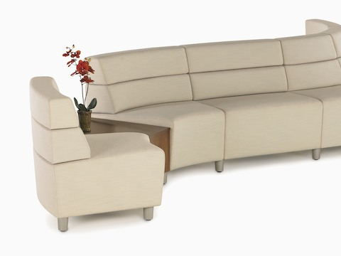 A curved configuration of beige, mid-back Steps Lounge System seating modules with an intervening surface.