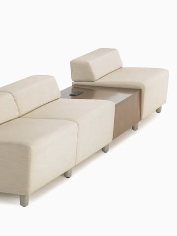 A straight configuration of three beige, low-back Steps Lounge System modules with an intervening surface offering power access.