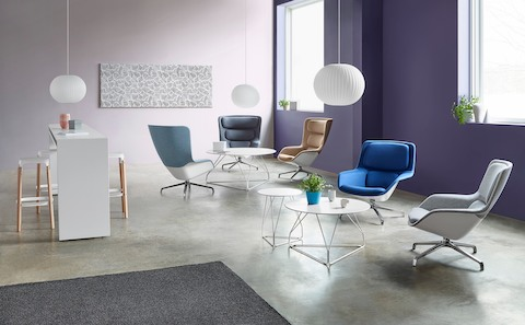 A sitting area featuring five Striad Lounge Chairs in shades of blue, beige, and gray, as well as round Polygon Wire Tables.