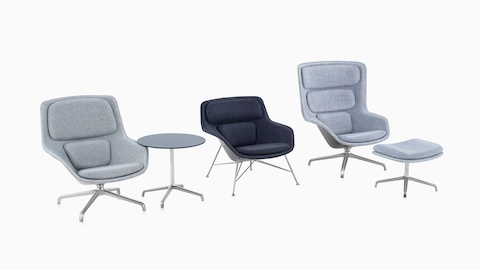 Low-back, mid-back, and high-back Striad lounge chairs upholstered in gray textiles line up, accompanied by a Striad Table and a Striad Ottoman.