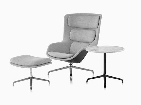 Striad High-Back Lounge Chair in a silver textile next to a Striad Table.