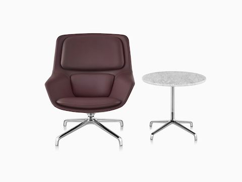 Burgundy leather Striad Mid-Back Lounge Chair with Striad Table with Carrara marble surface.