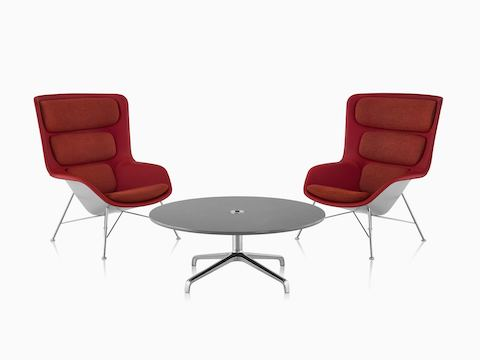 Two red and gray Striad High-Back Lounge Chairs with Striad Table with concrete quartz surface.