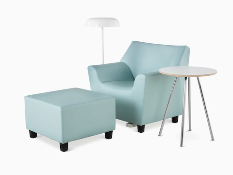 A Swoop Club Chair and Ottoman in a light green upholstery. A Swoop Work Table with a white top and chrome base. An Ode floor lamp in white. The Swoop Club Chair has an optional power unit and housing.