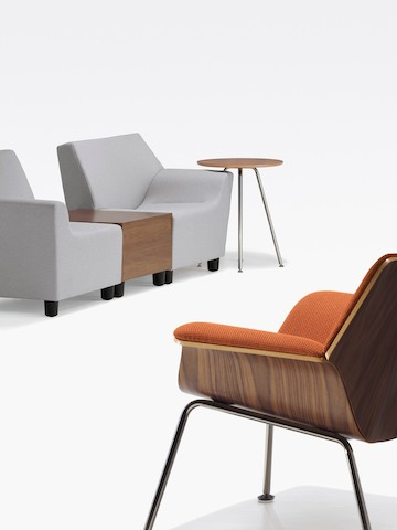 An orange Swoop lounge chair and two gray Swoop modular components on either side of a coordinating box table.