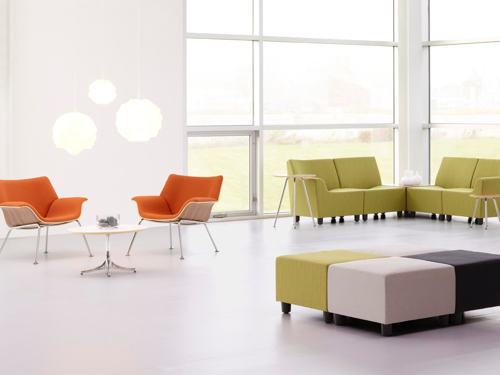Orange Swoop lounge chairs and green Swoop modular seating in a casual gathering space.