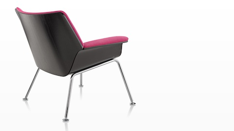 Three-quarter rear view of a Swoop lounge chair with magenta upholstery.