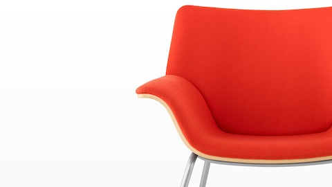 Close view of the sweeping curves on a red-upholstered Swoop lounge chair.