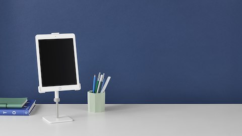 A Tabetha Tablet Mount elevates a tablet off a work surface that also supports a pen holder and reference materials.