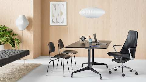An executive office featuring a black leather Taper Chair, rectangular Eames Table, and two Eames Molded Plywood Chairs.