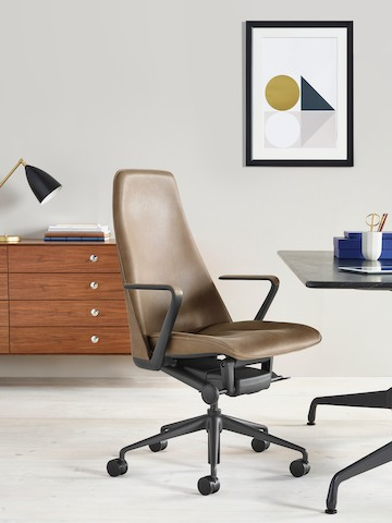 An executive office featuring a brown leather Taper Chair, rectangular Eames Table, and cabinet from the Nelson Thin Edge Group.