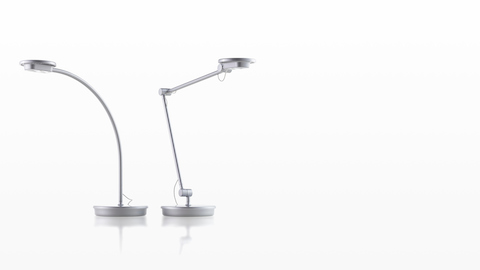 Two silver Tone Personal Lights, one with a single curved arm and one with an articulating arm.