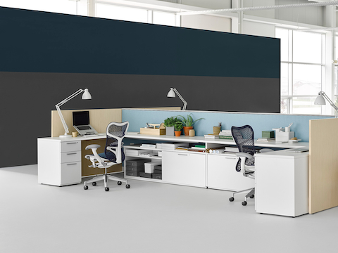 Tu storage components support the surfaces in a U-shaped open work area.
