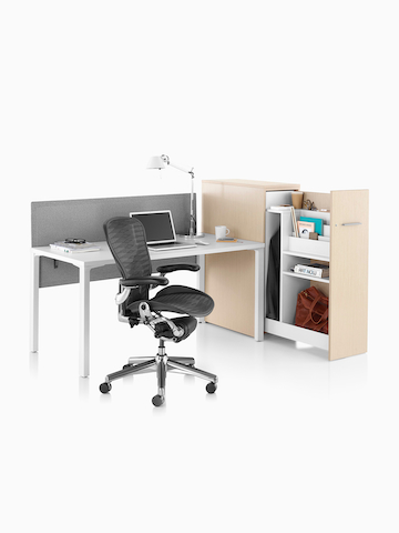A vertical Tu Storage unit and black Aeron office chair in an open workstation. Select to go to the Tu Storage product page.