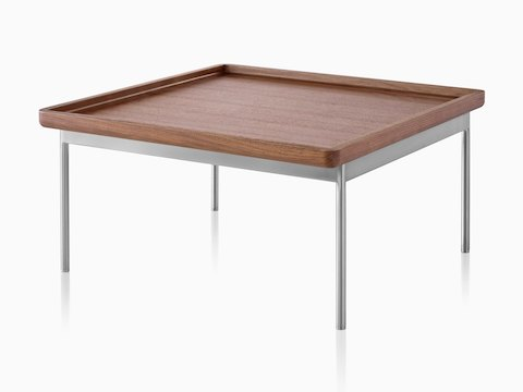 An angled view of a rectangular Tuxedo Table with a medium woodgrain finish and silver metal base.