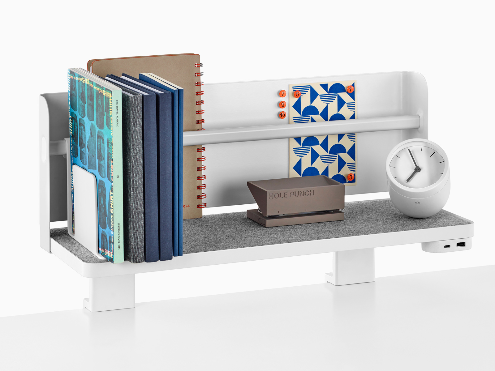 A Ubi Attached Shelf with a backdrop supports books, a hole punch, a desk clock, and a USB power module.