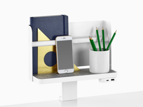 A Ubi Attached Shelf with a backdrop supports a book, smartphone, pencil cup, and USB power module.