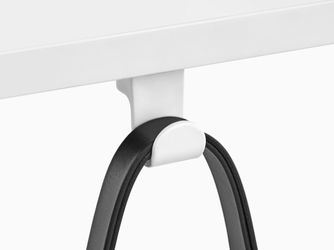 A black strap loops over a fixed Ubi Bag Hook affixed to the underside of a work surface.