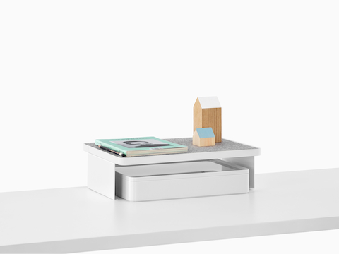 A Ubi Freestanding Shelf with personal items on top and a storage box below.