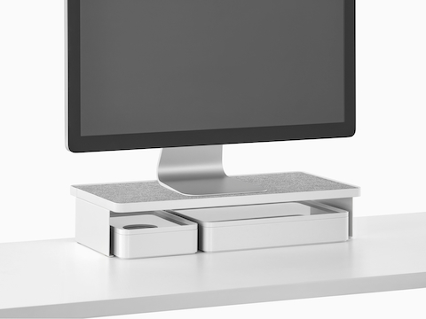 A freestanding monitor sits on a Ubi Monitor Platform Shelf with two storage boxes below.