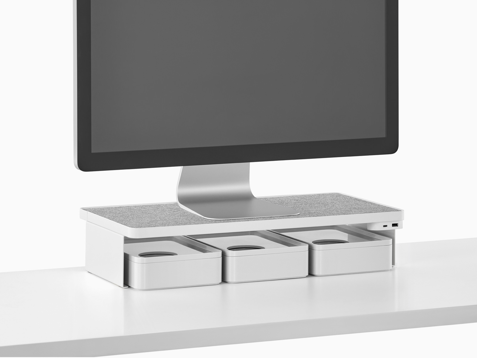 A freestanding monitor sits on a Ubi Monitor Platform Shelf with a USB power module and three storage boxes below.