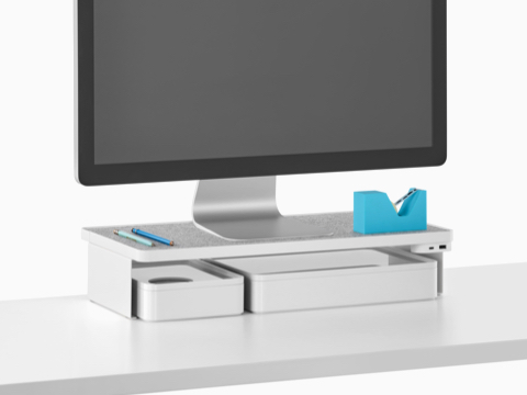 A freestanding monitor sits on a Ubi Monitor Platform Shelf with a USB power module and two storage boxes below.
