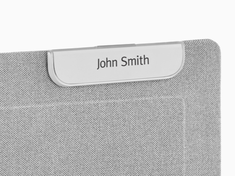 A Ubi Name Tag attached to a fabric-covered panel.