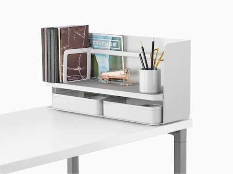 A small white Ubi desktop organiser with a grey non-skid shelf holds books, a stapler, a pencil cup, and two storage boxes.
