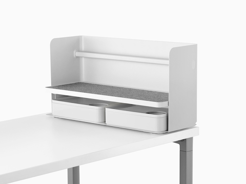 A small white Ubi desktop organiser with a grey non-skid shelf and two storage boxes.