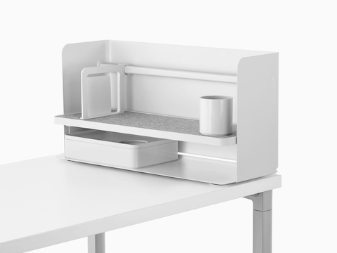 A small white Ubi desktop organiser with a bookend, pencil cup, grey non-skid shelf, and storage box.