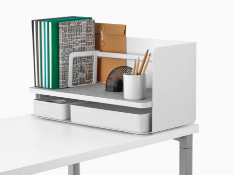 A large white Ubi desktop organiser with a grey non-skid shelf holds books, a pencil cup, and two storage boxes.