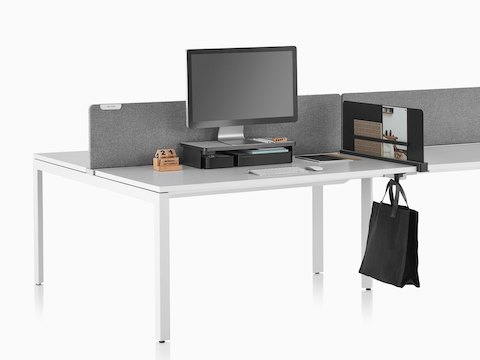 A work surface equipped with Ubi Work Tools, including a black monitor platform shelf, slim screen, and bag hook.