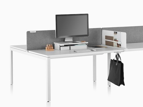 A work surface equipped with Ubi Work Tools, including a white monitor platform shelf, slim screen, and bag hook.