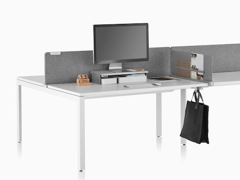 A work surface equipped with Ubi Work Tools, including a gray monitor platform shelf, slim screen, and bag hook.