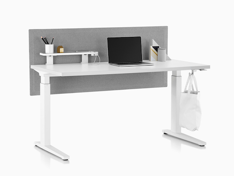 A rectangular sit-to-stand table equipped with Ubi Work Tools, including an attached shelf, USB power module, and bag hook.