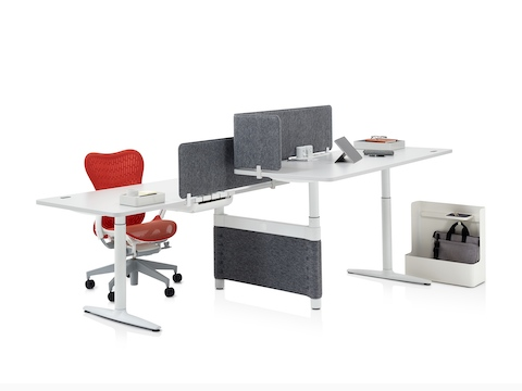 A workspace featuring a red Mirra 2 office chair, two height-adjustable desks, and various Ubi Work Tools to aid organisation.