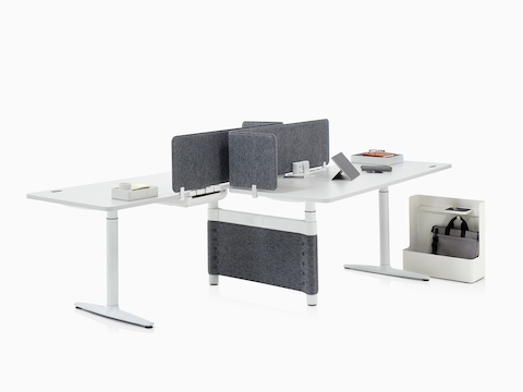 Two height-adjustable desks support various Ubi Work Tools to aid office organization, including a Ubi Mobile Bag Catch.