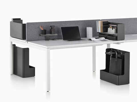 A work surface equipped with Ubi Work Tools, including an attached shelf, desktop organizer, and mobile bag catch.