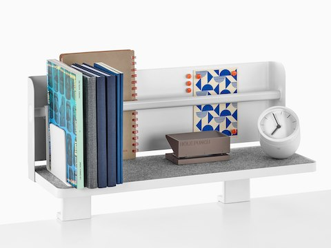 A Ubi Attached Shelf with a backdrop supports a small clock, hole punch, books, and other reference materials.