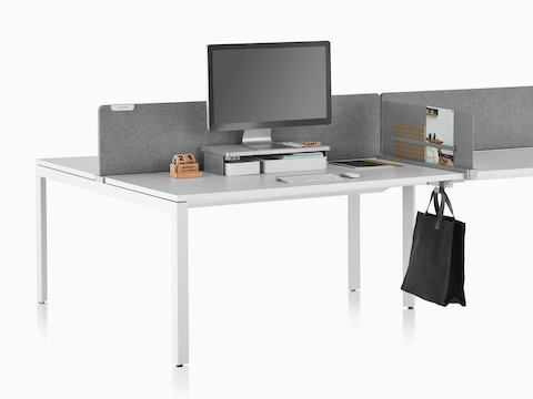 A work surface equipped with Ubi Work Tools, including a monitor platform shelf, slim screen, and bag hook.