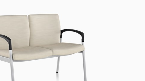 Angled view of two-seat Valor Multiple Seating with beige upholstery, a steel frame, and black arms.