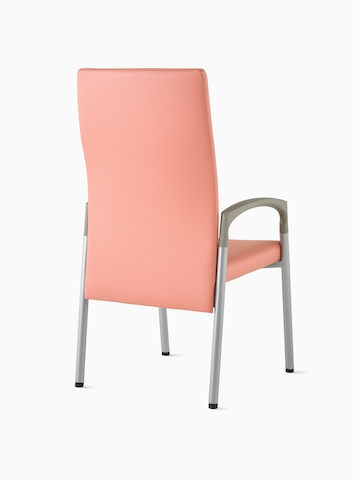 Three-quarter, back view of a high-back Valor Patient Chair in a salmon pink upholstery and silver frame with pewter armcaps.