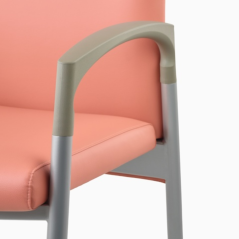 Detail of a silver frame and pewter armcap on a Valor Patient Chair upholstered in salmon pink.