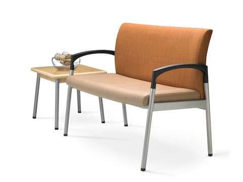 Angled view of extra-wide Valor Plus Seating with an orange back and beige seat, positioned next to a square end table.