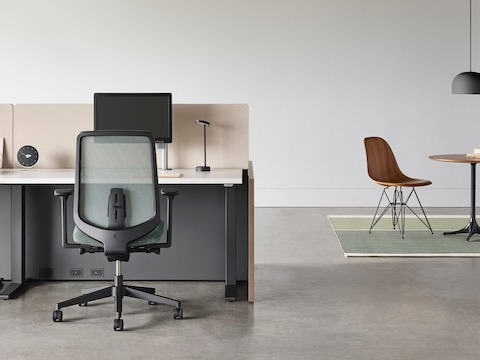 A black Verus chair with a black Motia Sit-to-Stand Table and Canvas Channel workstation with a Nelson Pedestal Table and Eames Molded Wood Side Chair in the background.