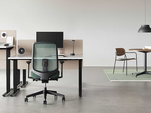 A black Verus Chair with dark green suspension back pulled up to a black Nevi Sit-Stand Desk with a Civic Table and Portrait Chair in the background.