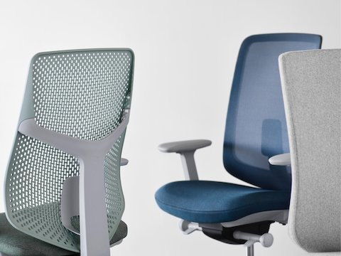 A close-up view of a Verus Chair with a green Triflex back, a Verus Chair with a blue upholstered seat and blue suspension back, and a Verus Chair with a gray upholstered back.